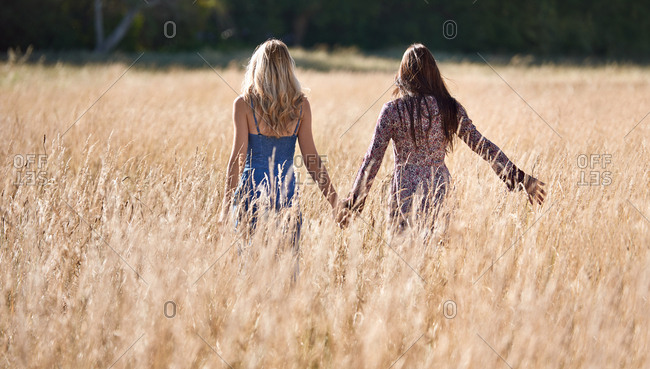 Back view of girls going for a walk in long grassy field healthy lifestyle wellness