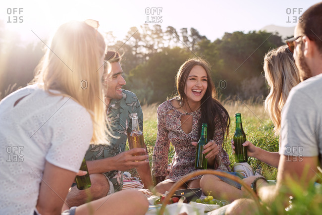 Happy carefree friends smiling laughing talking enjoying picnic in a field at sunset, healthy summer lifestyle