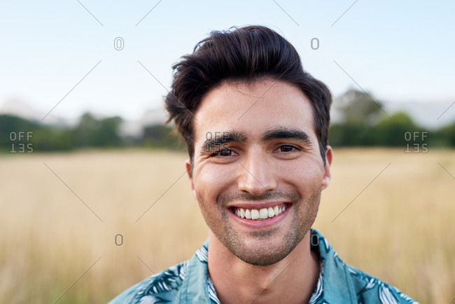 Close up portrait of real man smiling at camera, happy carefree on in nature outdoors summer days