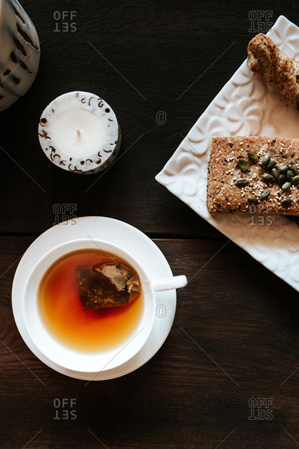 Tea and seeded bread on table with candles