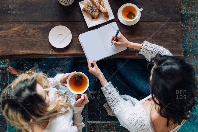 Two women drinking tea and working together at home
