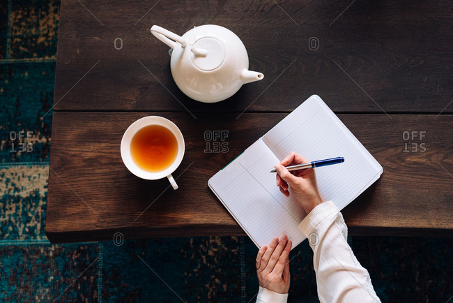 Aerial shot of hands writing something down in notebook on the big wooden table with tea cup and tea pot