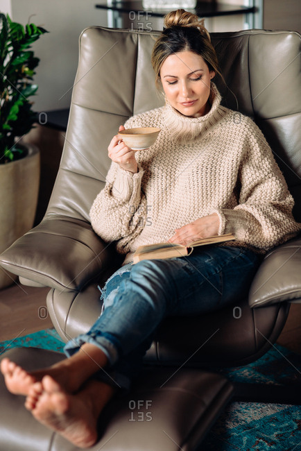 Blonde woman sitting in big cozy chair drinking tea and reading a book