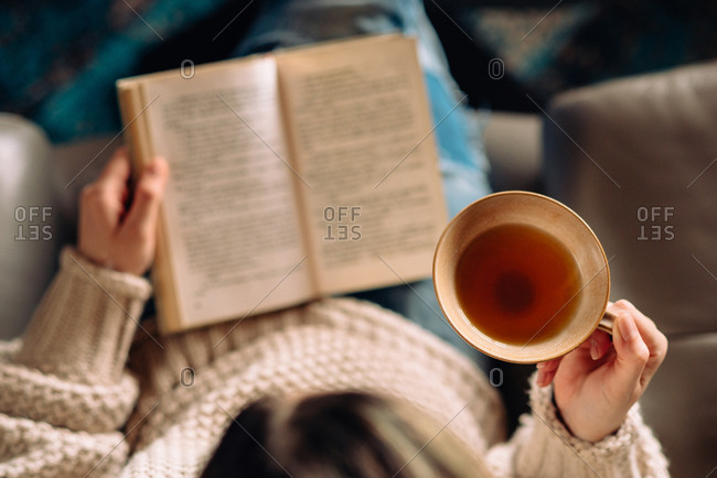Woman reading a book and holding a cup of tea