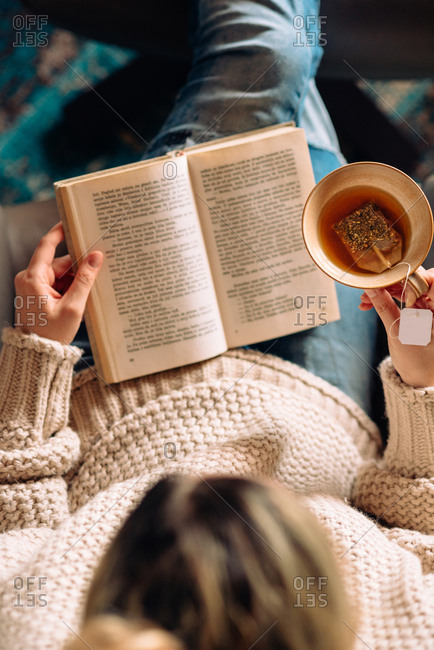 Aerial shot of woman reading a book and holding a cup of tea