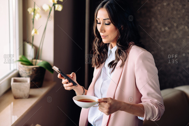 Young business woman drinking tea while texting on her phone