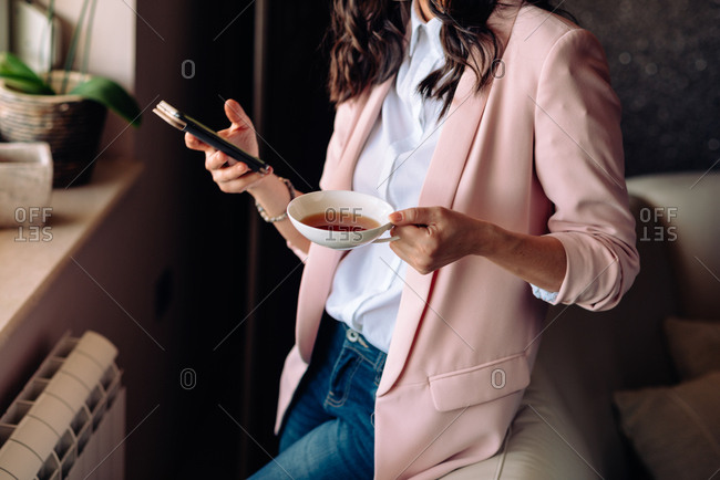 Woman drinking tea while texting on her phone