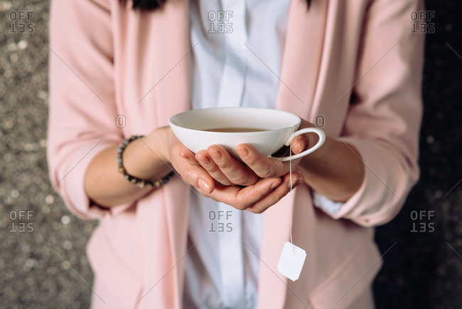 Close up of hands holding a cup of tea