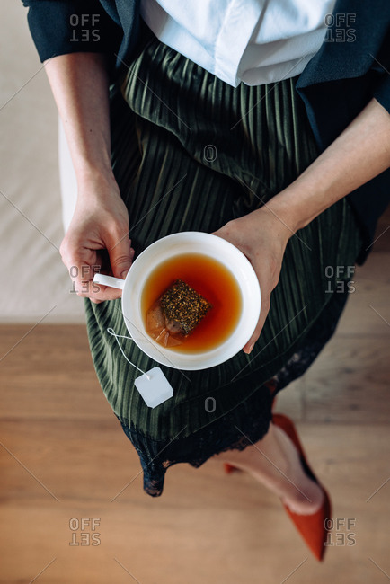 Aerial shot of woman holding a cup of herbal tea