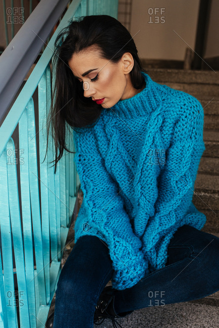 Woman in beautiful knitted turquoise sweater on stairs