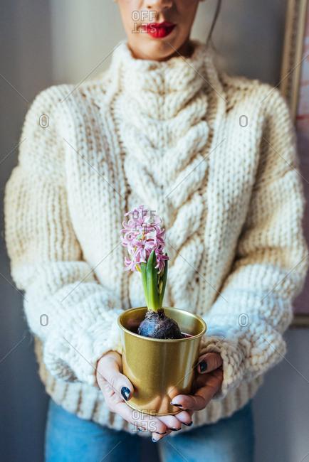 Woman in oversized wool sweater holding flowers