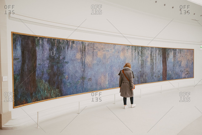 Paris, France - November 20, 2017: Woman viewing Claude Monet's Water Lilies in the oval room at Musee de l'Orangerie