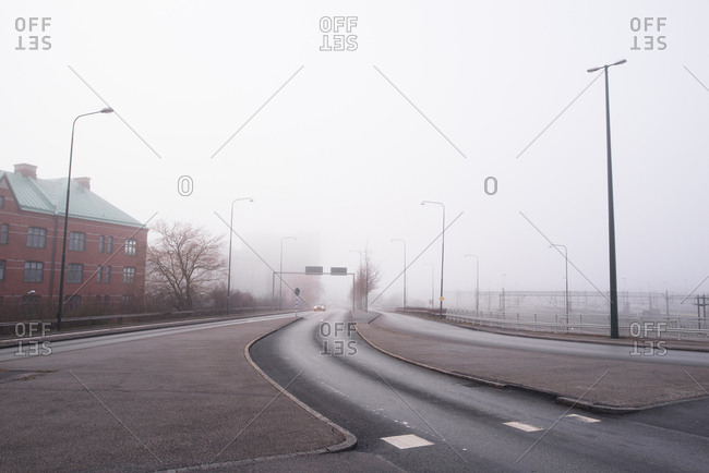 Car in the distance travelling on fog shrouded road