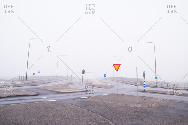 Fog shrouded crossroads with a confusion of road signs