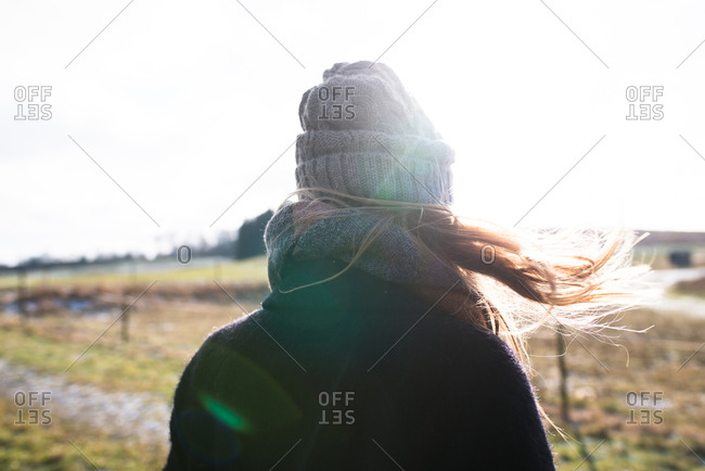 Rear view of solitary woman looking out over fields