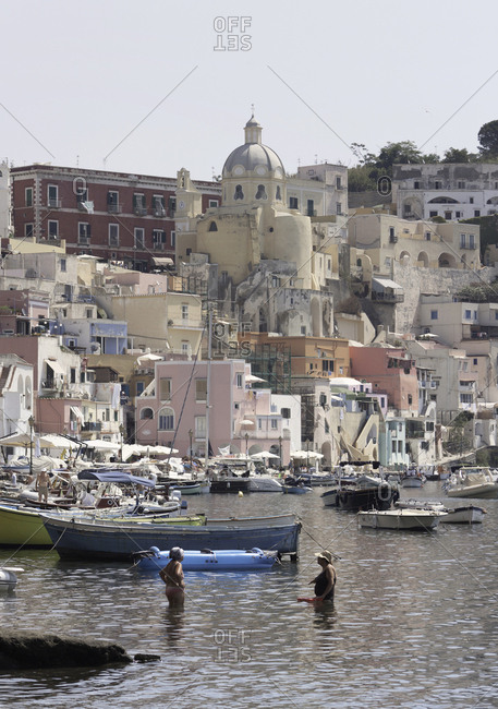Campania, Italy - July 19, 2017: Women bathing in the harbor of Coricella on the island of Procida, Campania, Italy