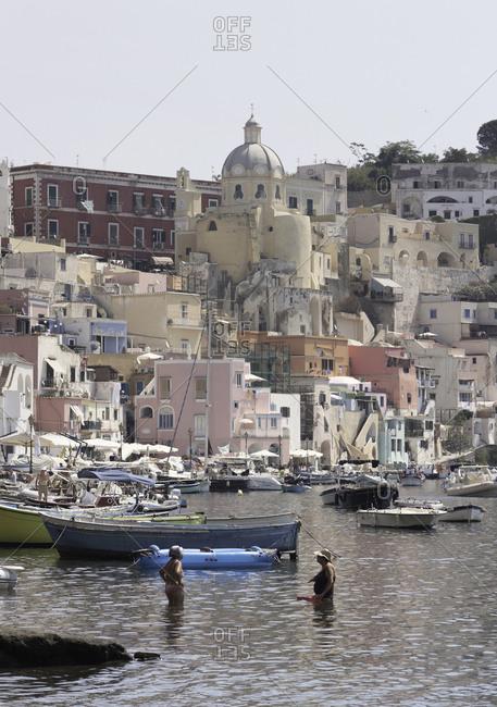 Campania, Italy - July 19, 2017: Women bathing in the harbor of Coricella on the island of Procida, Campania, Italy