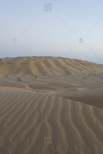 Lone vehicle in the desert dunes of the Empty Quarter, Oman