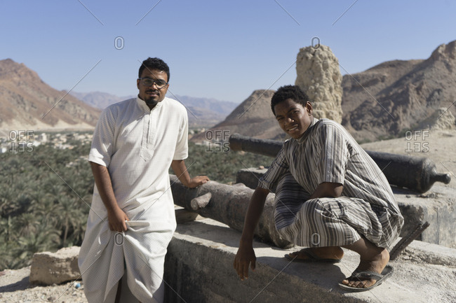 Fanja, Oman - November 19, 2016: Two men next to old cannons