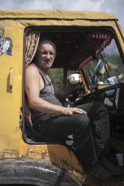 Ural Mountains, Russia - July 23, 2013: A truck driver takes a coffee break in the Ural Mountains, Russia