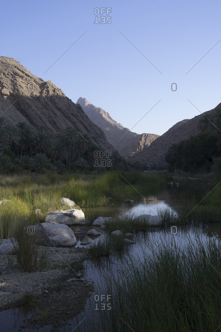Picturesque valley of Wadi Bani Khalid in Ash Sharqiya North, Oman, beneath the rugged slopes of Jebel Khadar