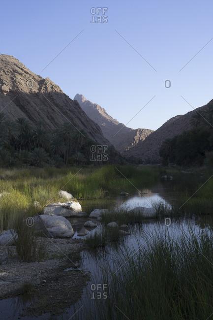 Picturesque valley of Wadi Bani Khalid in Ash Sharqiya North, Oman, beneath the rugged slopes of Jebel Khadar