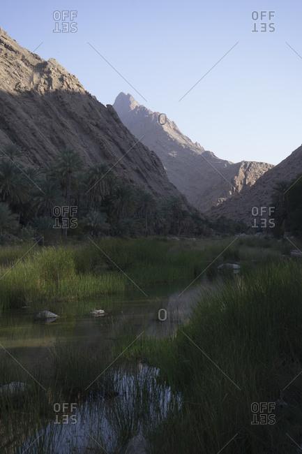 Wadi Bani Khalid in Ash Sharqiya North, Oman, stretched beneath the rugged slopes of Jebel Khadar