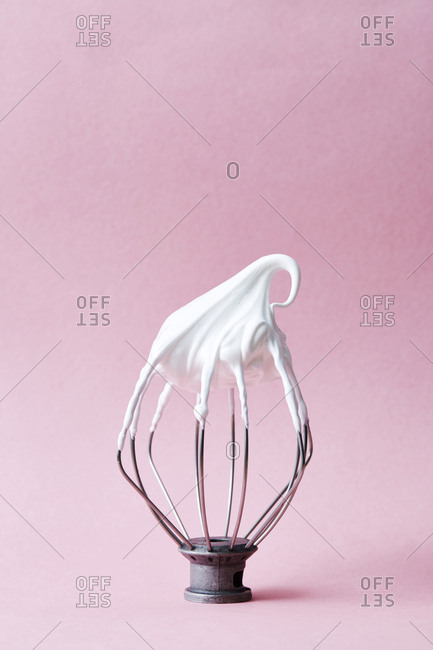 Beater with whipped cream on pink background