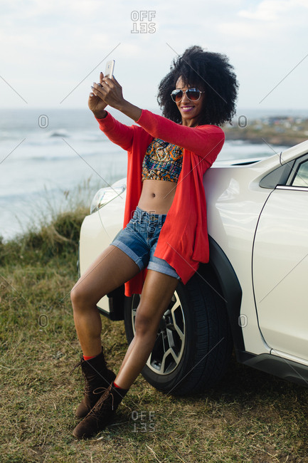 Fashionable afro hair woman on vacation taking selfie photo with smartphone towards the sea. Stylish black model enjoying a car trip to the coast.