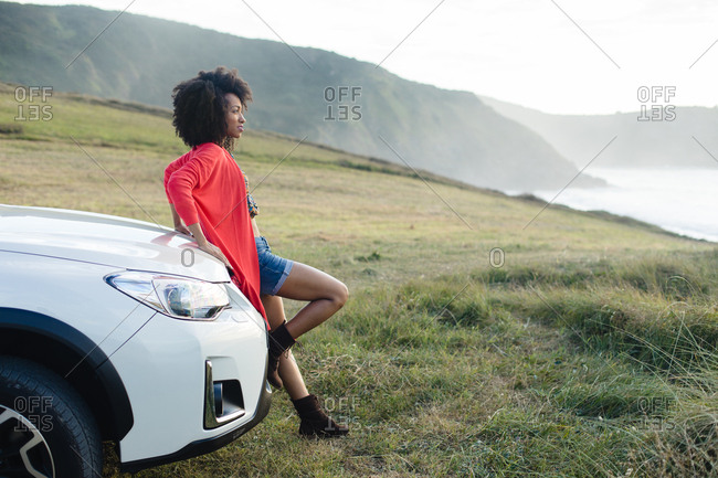 Stylish black woman relaxing on car trip in Asturias coast, Spain. Fashionable afro hair model on vacation towards the sea.