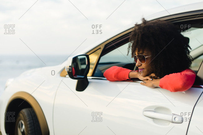 Stylish black woman relaxing on a car trip to the coast. Fashionable afro hair model on vacation towards the sea.