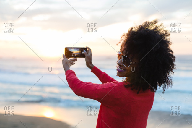 Happy fashionable afro hair woman taking photo to the sunset and the sea with smartphone camera. Stylish black model enjoying a trip to the coast.