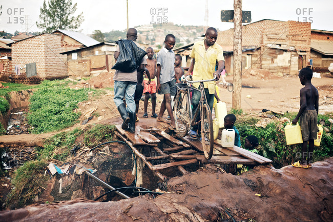 Kampala, Uganda - September 26, 2011: Local people is crossing an alternative bridge, which is made by broken wood pieces in the Kamwookya neighborhood of Kampala. The Kamwookya neighborhood is known as a slum district and for low living standards.