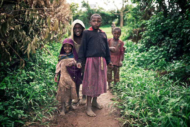 Lake Bunyonyi, Uganda - September 17, 2011: A group of smiling local kids seen on a dusty path close to the Lake Bunyonyi, which is also known as the Place of Many Little Birds.