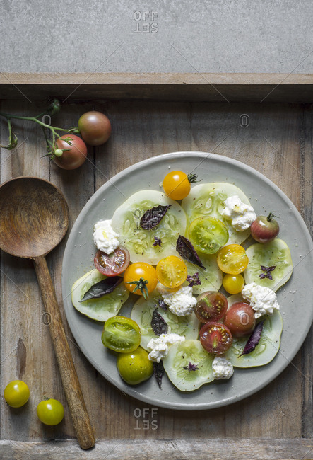Tomato cucumber salad with burrata and purple basil on a grey ceramic plate with a serving spoon on a wooden tray.