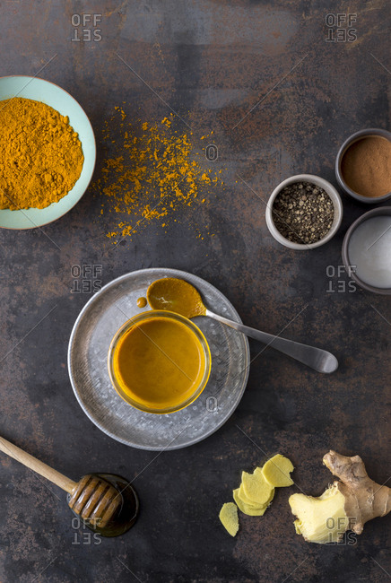 Turmeric-filled golden paste in a jar with a spoon and ingredients