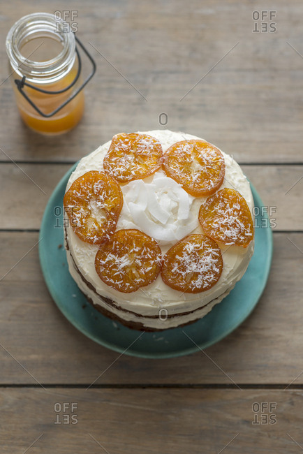 A parsnip cake with clementine cream frosting, candied clementines and coconut flakes.