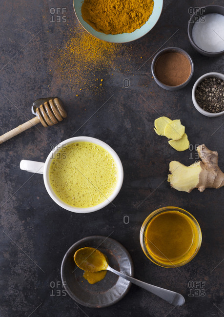 Turmeric-based golden milk in a mug surrounded by ingredients.
