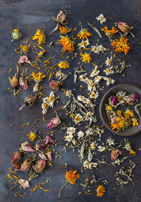 An array of loosely strewn dried flowers and herbs for an herbal tea blend with a sample in a metal dish.