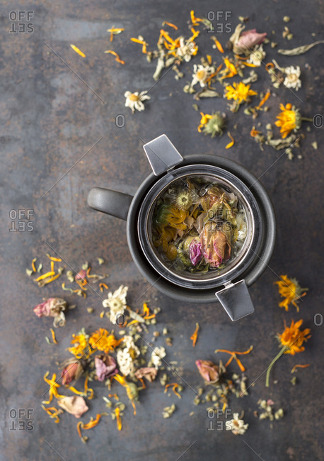 A cup of herbal tea with a strainer filled with dried herbs and flowers and plant material on the surface.
