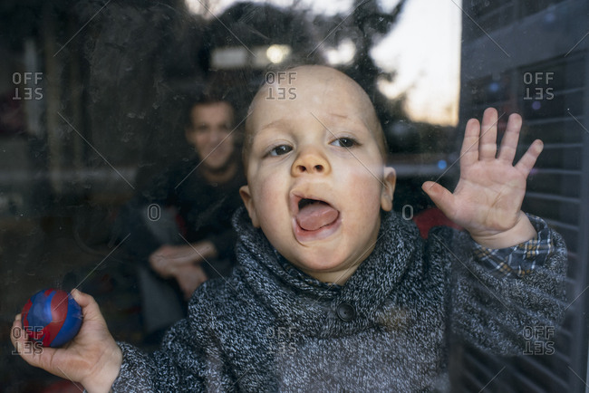 Boy presses mouth against window