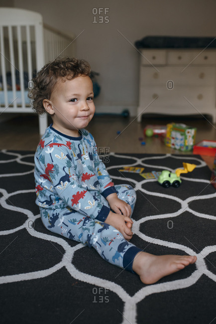 Toddler boy wearing pajamas sits on rug