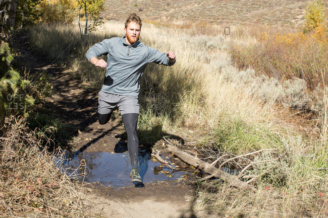 Man running through wilderness and jumping over a small body of water
