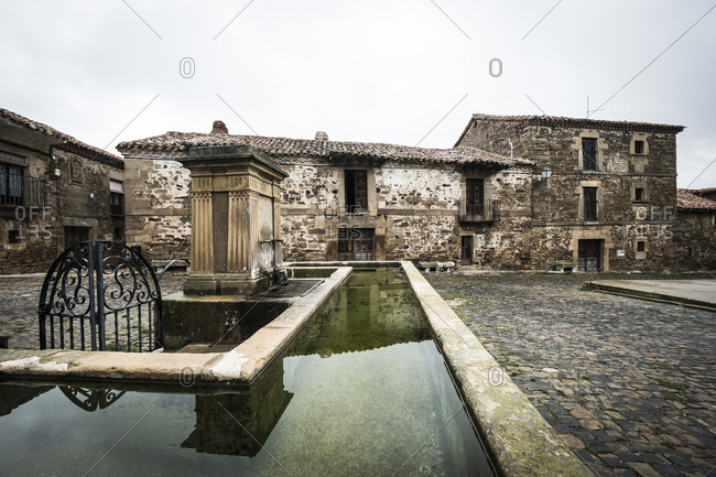Castilfrio de la Sierra, Spain - November 4, 2017: Stone watering trough in cobblestone plaza in the town