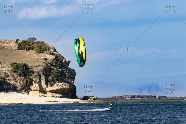Lombok, Indonesia - July 24, 2017: Man kite boarding in a lagoon on dramatic coastline