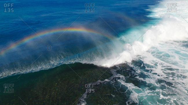 Aerial view of powerful wave breaking on shallow reef and rainbow
