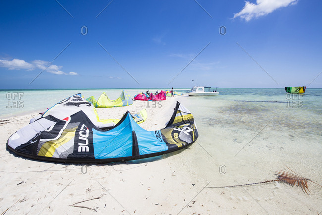 Wakatobi, Indonesia - July 15, 2015: Colorful kite surfing kites laid out on sand bar ready for use