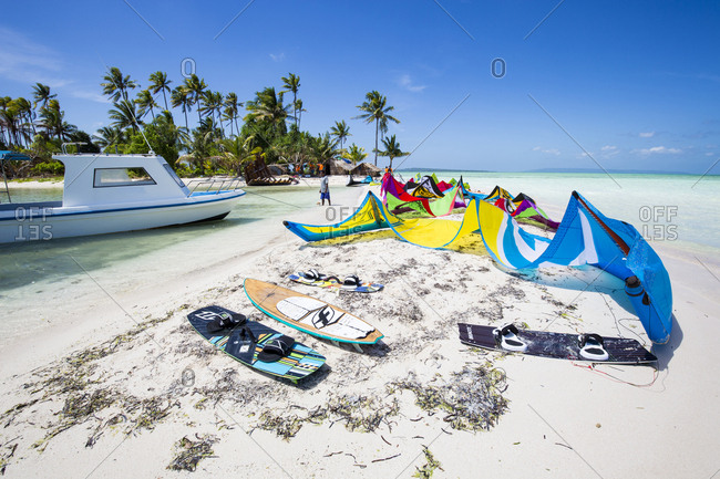 Wakatobi, Indonesia - July 15, 2015: Kite surfing equipment laid out on a white sand beach