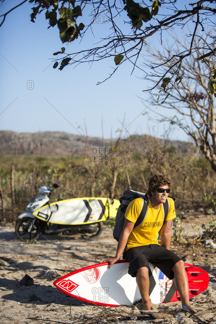 Sumbawa, Indonesia - September 09, 2016: Australian Keahi De Aboitiz sitting on surfboard at beach checking wind and surf conditions