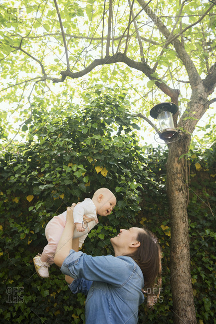 Caucasian mother lifting baby daughter under tree
